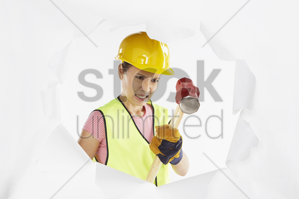 construction worker using hammer to make a hole in the wall stock photo