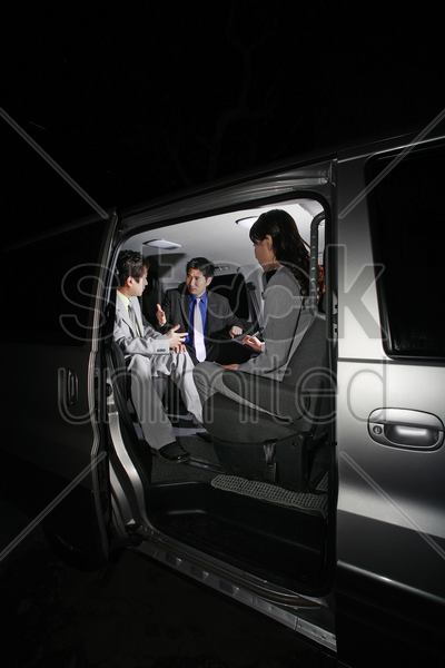 corporate people having discussion in the car stock photo