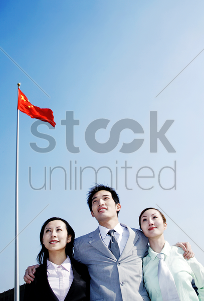corporate people standing under a flag stock photo