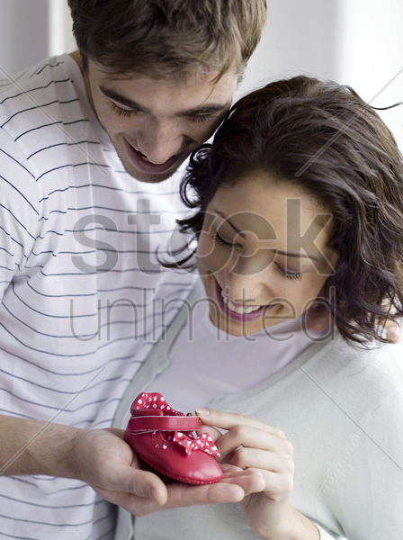 couple admiring a red baby's shoe stock photo