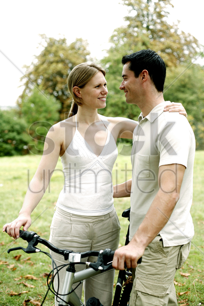 couple and a bicycle in the park stock photo