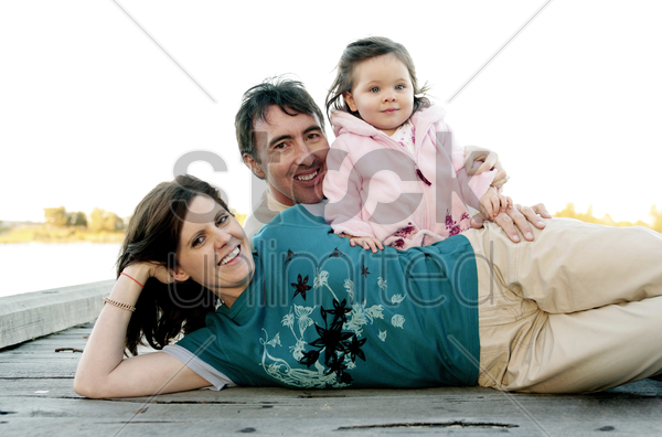 couple and their daughter posing for the camera stock photo