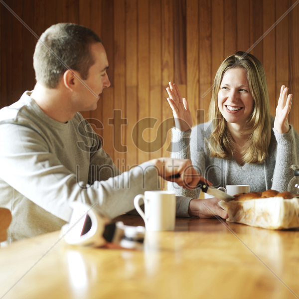 couple chatting while having breakfast together stock photo