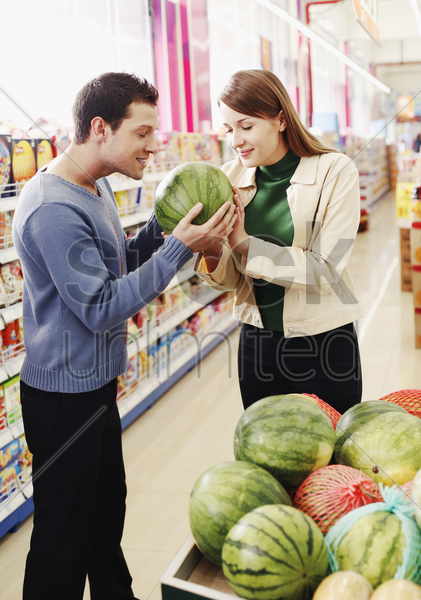 couple choosing water-melon in the supermarket stock photo