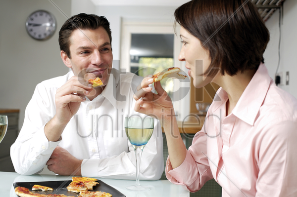 couple eating pizza together stock photo