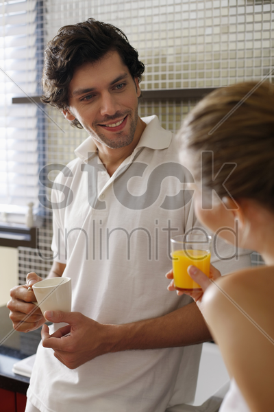 couple enjoying beverages in the kitchen stock photo