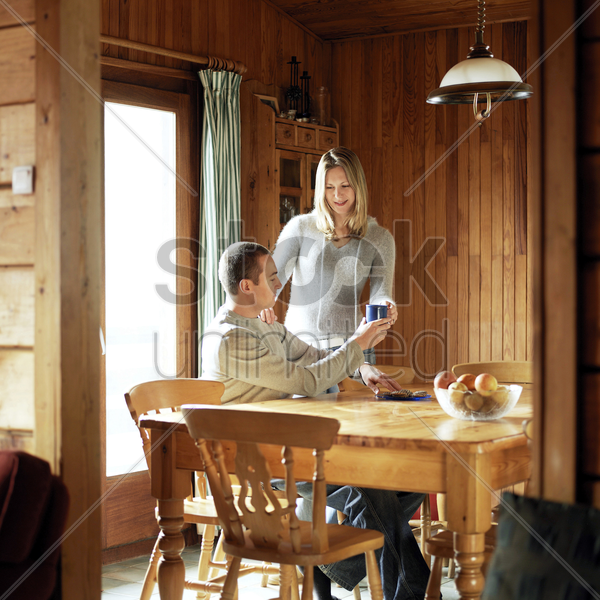 couple enjoying hot drinks in the chalet stock photo