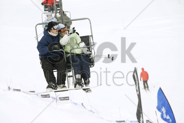 couple enjoying the view from chair lift stock photo