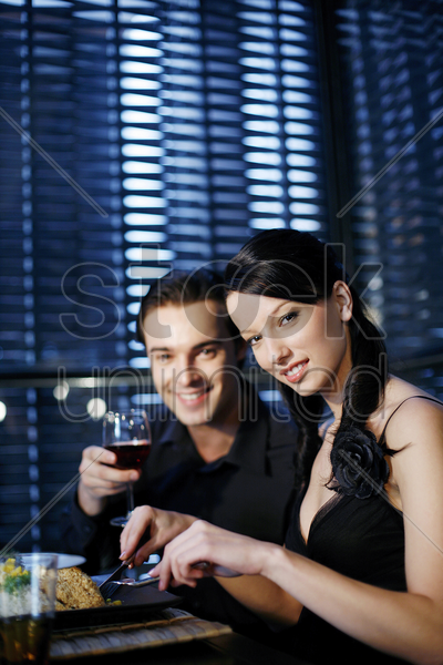 couple enjoying their meal in a restaurant stock photo