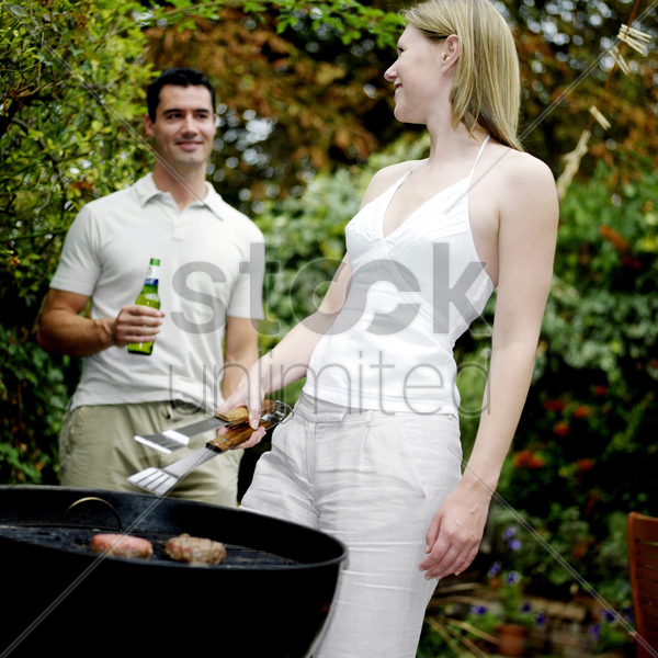 couple grilling food in the park stock photo