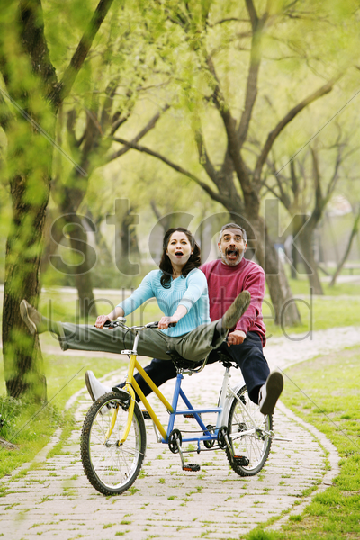 couple having fun cycling in the park stock photo