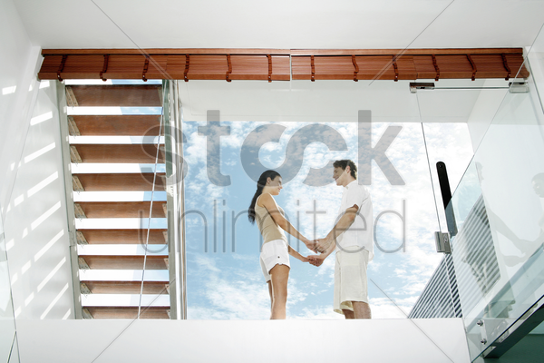couple holding hands on the balcony stock photo