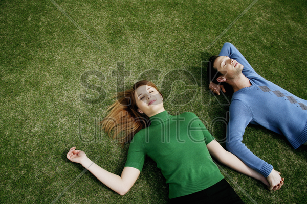 couple holding hands while lying on the field stock photo