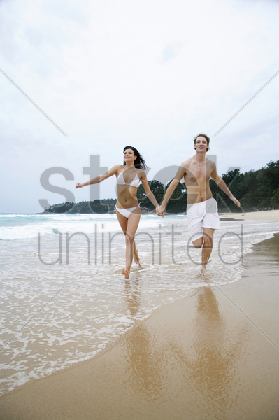 couple holding hands while running on the beach stock photo
