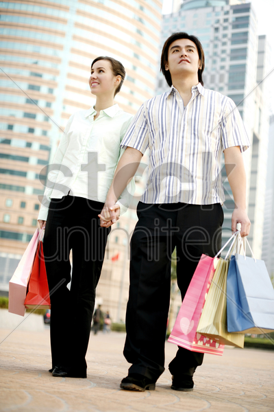 couple holding hands while shopping stock photo