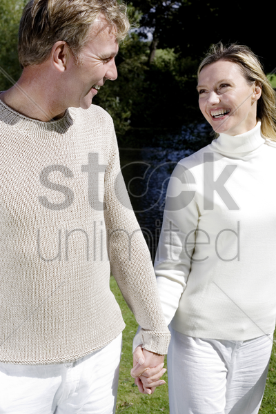 couple holding hands while walking in the park stock photo