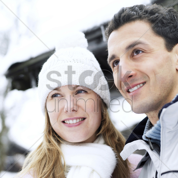 couple in warm clothing looking away stock photo