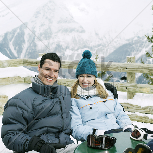couple in warm clothing smiling at the camera stock photo