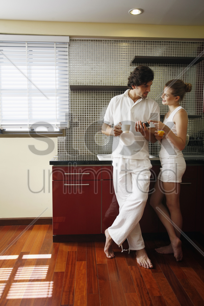 couple looking at text message while enjoying beverages stock photo