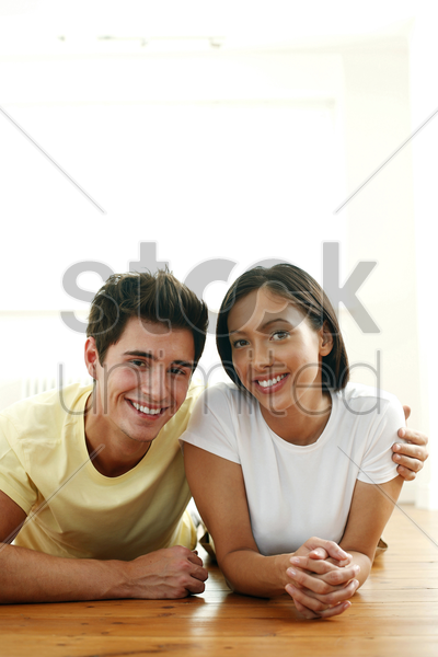 couple lying forward on the floor smiling at the camera stock photo