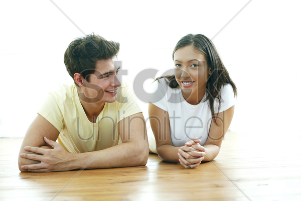 couple lying forward on the floor smiling stock photo