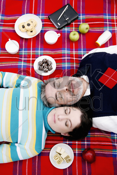 couple lying on picnic blanket stock photo