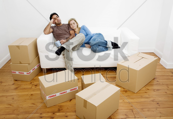 couple napping on the couch with boxes on the floor stock photo