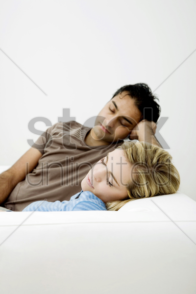 couple napping on the couch stock photo