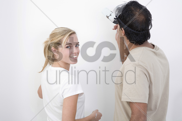 couple painting the wall stock photo