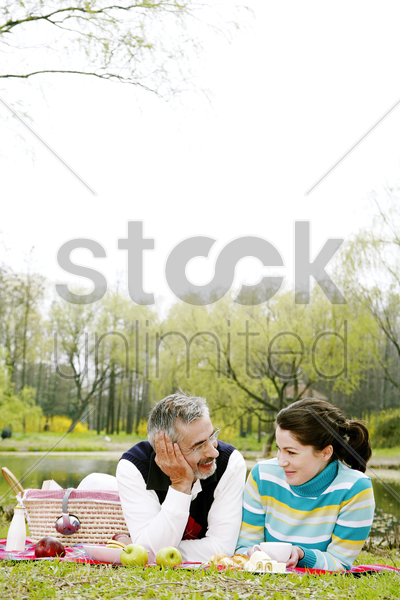 couple picnicking in the park stock photo