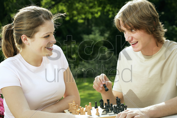 couple playing chess game stock photo