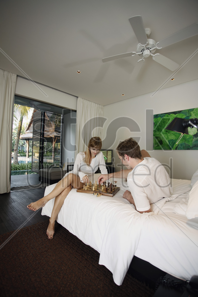couple playing chess in resort bedroom stock photo