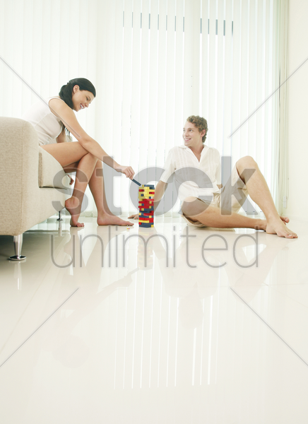 couple playing plastic blocks at home stock photo