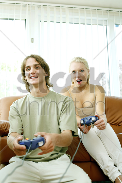 couple playing video game console stock photo