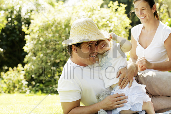 couple playing with their baby daughter in the park stock photo