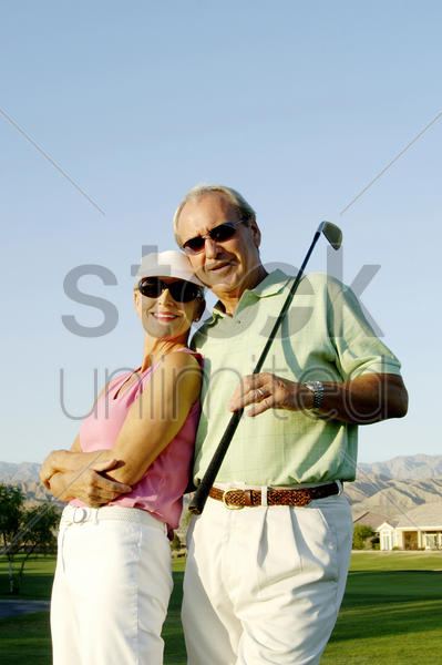 couple posing in the golf course stock photo