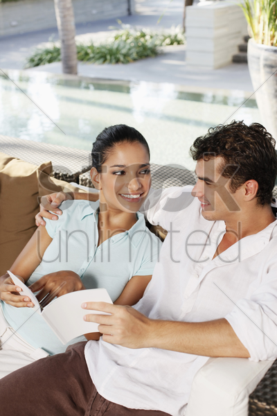 couple reading book together stock photo