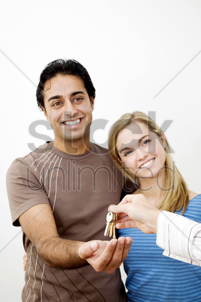 couple receiving key to their new house stock photo