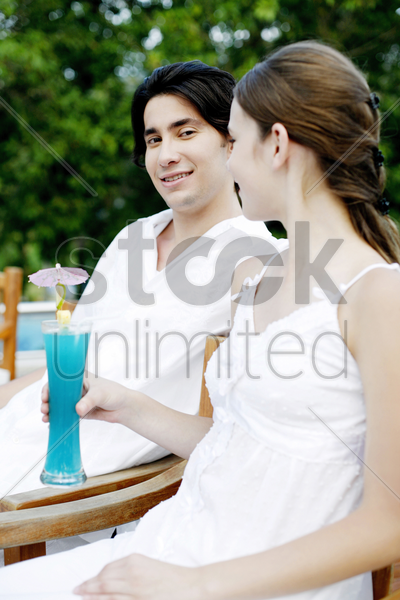 couple relaxing by the pool side stock photo