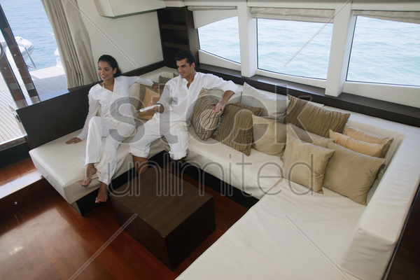 couple relaxing in yacht living room stock photo