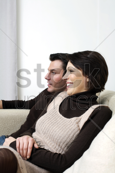 couple resting on the couch stock photo