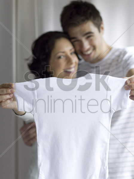 couple showing a white onesie stock photo