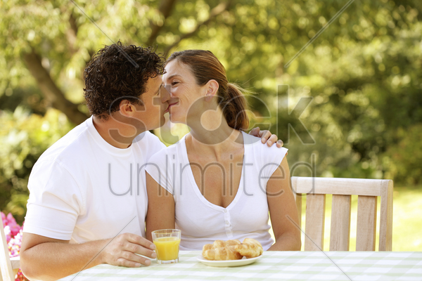 couple sitting at the picnic table kissing stock photo