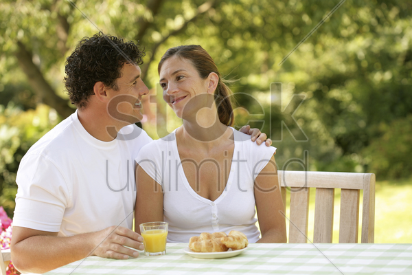 couple sitting at the picnic table looking at each other stock photo