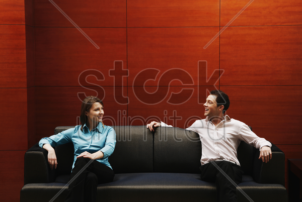 couple sitting on the couch talking stock photo