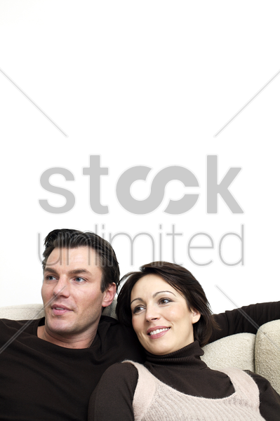 couple sitting on the couch stock photo