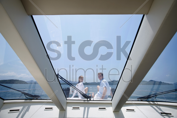 couple sitting on yacht deck stock photo