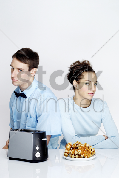 couple sitting together with toaster and waffles on the table stock photo
