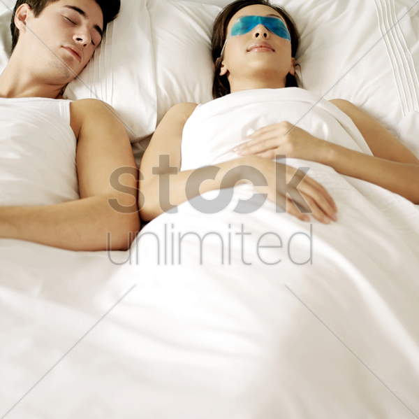 couple sleeping on the bed stock photo
