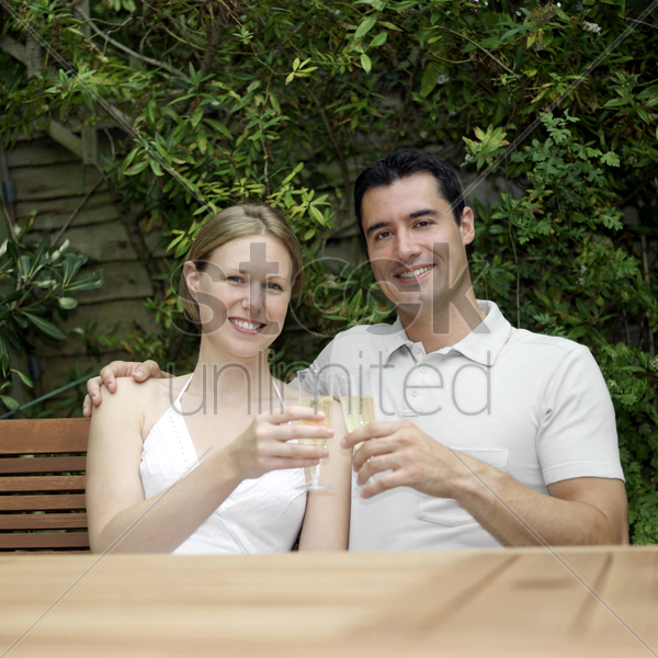 couple smiling at the camera while holding glasses of champagne stock photo